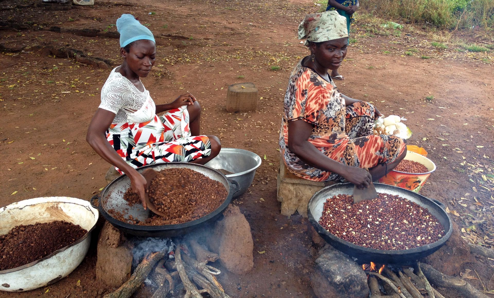 Two women roasting shea and ground nuts in Murugu, Ghana